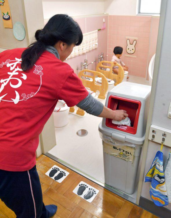 写真はトイレに置かれたごみ箱に使用済みおむつを捨てる保育士=2018年2月、東京都品川区立大井保育園で(由木直子撮影)