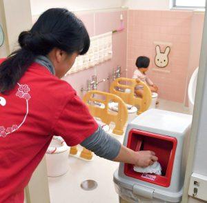 写真はトイレに置かれたごみ箱に使用済みおむつを捨てる保育士=2月、東京都品川区立大井保育園で(由木直子撮影)