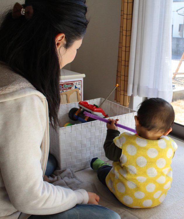 写真は育休の延長を決めた女性。復帰後の過酷さも理由の一つという=埼玉県内で