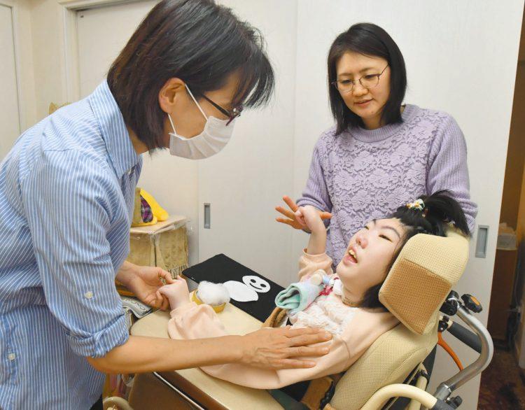 写真は自宅で特別支援学校の下田恵子教諭(左)の授業を受ける福満華子さん。奥は母の美穂子さん=東京都中野区で