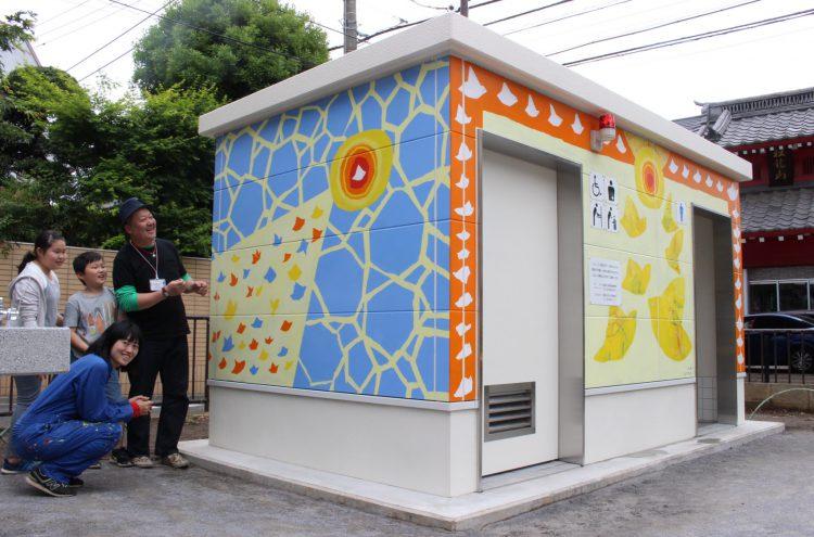 写真 朝日に向かって飛ぶ鳥を描いたトイレの完成を喜ぶ椎木彩子さん(左手前)と地元小学生の親子