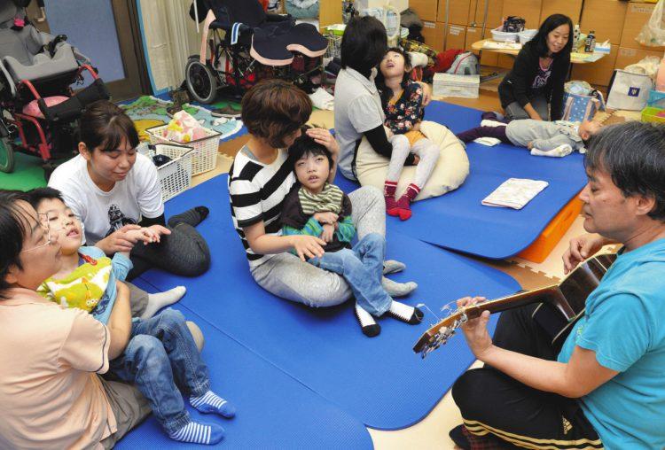 写真は「おでんくらぶ」で看護師らに付き添われて音楽を聴く子どもたち=2017年10月、東京都中野区で