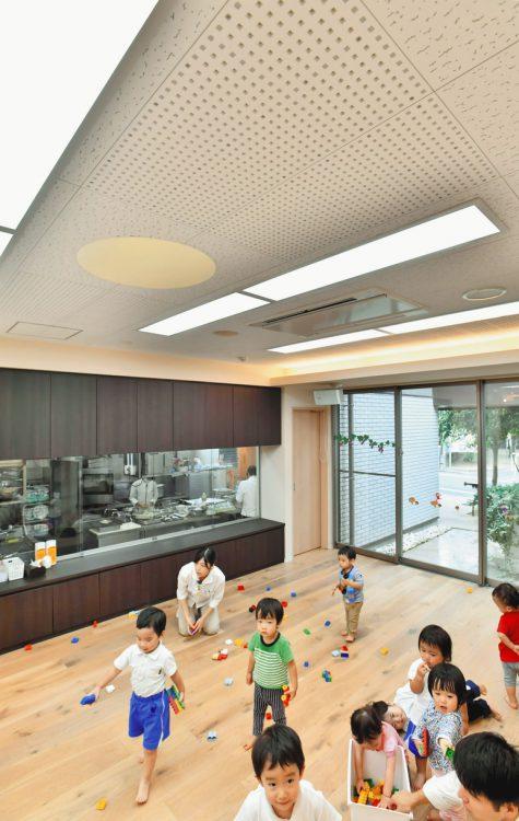 写真 吸音材が設置された天井部分(ドット状の部分)の保育室で遊ぶ子どもたち 東京都練馬区で