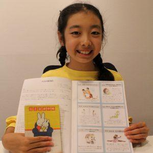 子どもの権利条約を説明する冊子と自身の母子手帳を手に話す坂口くり果さん