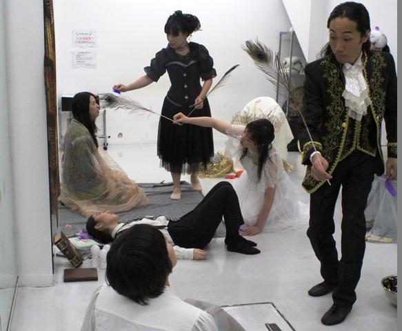 写真 子ども役のスタッフを相手に小道具の羽の動きを確認する出演者たち
