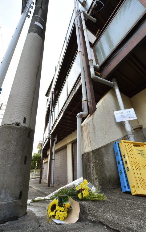 女児が虐待を受けた建物の前に供えられた花束
