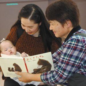 写真 ボランティア(右)から本を紹介してもらうチンさん母娘=茨城県牛久市で