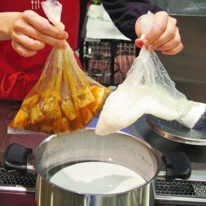 写真 「お湯ポチャ料理」で麻婆高野豆腐とご飯を作る今泉マユ子さん=東京都内で