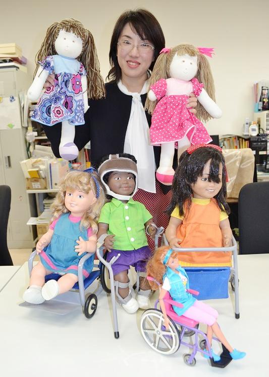写真 水野智美さんが集めた障害者の人形。手にしている人形はブラジル製。車いす、つえ、歩行器の人形はドイツ製。一番手前はバービー人形の親友で、車いすのベッキー人形