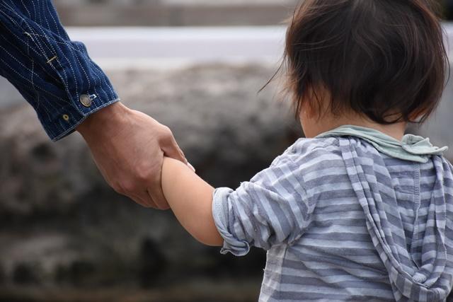 子どもの手をとる親