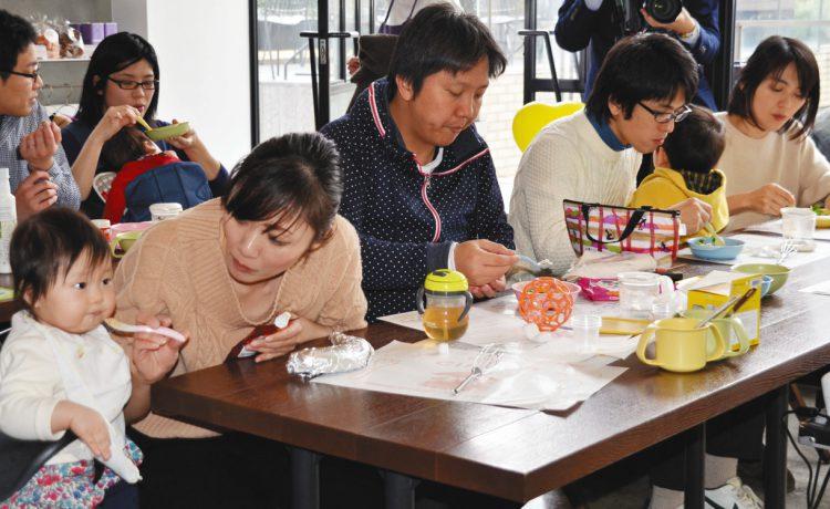 写真 離乳食を試食する親子ら=東京都渋谷区で