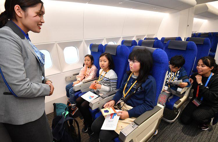写真 エアプレイン(飛行機)ではキャビンアテンダントに、毛布や飲み物を持ってきてもらうよう頼む