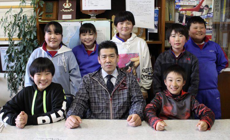 元校長の西野さん(前列㊥)を囲み、給食を食べた野友小の子どもたち