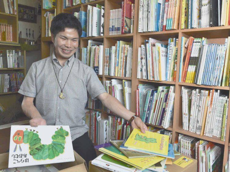 支援用の絵本を仕分ける「こども古本店」の中島英昭さん=愛知県北名古屋市で