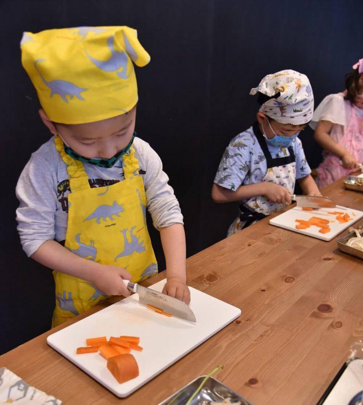 料理教室で包丁を使って野菜を切る子どもたち