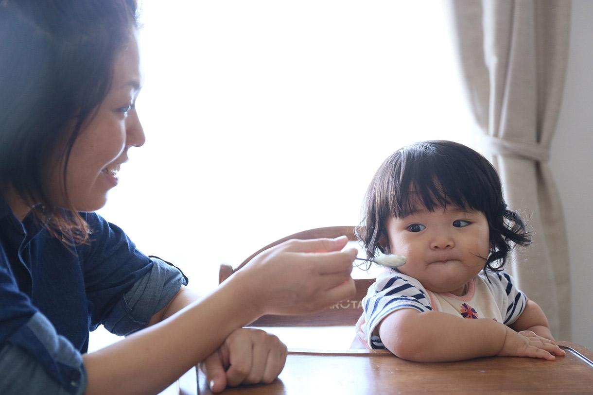写真 子どもの食事の世話をする母親
